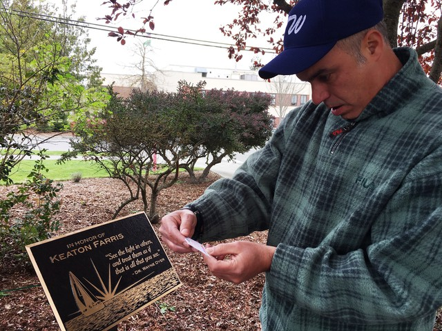Fred Farris reads a note left at a memorial for his son Keaton who died in the Island County Jail in 2015.