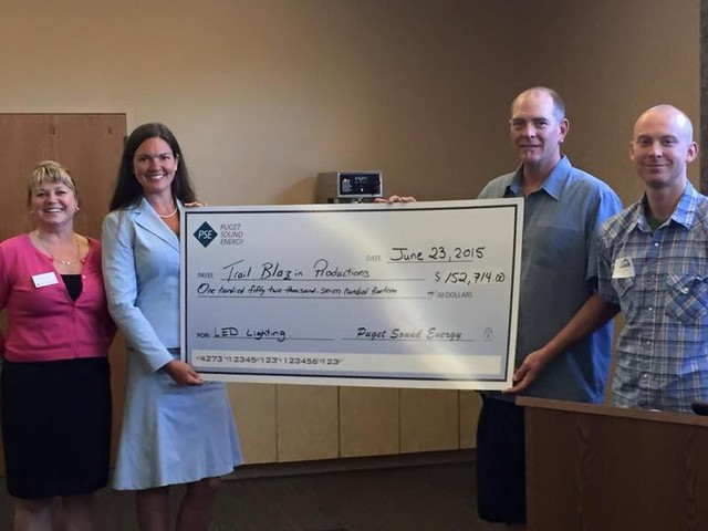 Danielle and Juddy Rosellison accept giant rebate check as PSE employees look on.