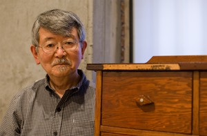 Richard Koyama next to a chest his father made
