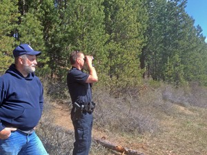 Darin Bean looks through binoculars at Twin Lakes while chatting with La Pine resident and fisherman Larry Archer. Bean cited Archer in the past for shooting a wildlife decoy.