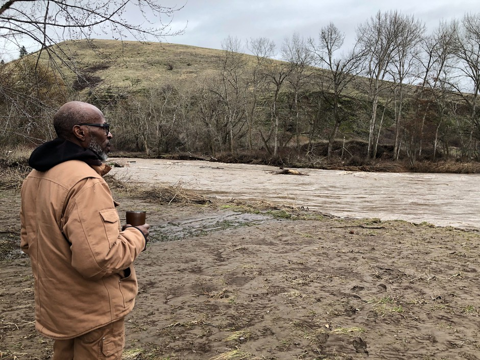 Leroy Cunningham, of Waitsburg, Washington, looks at the Touchet River behind his near century-old farmhouse. Cunningham says he and his husband lost their fine Northwest wine collection in the flooded cellar, but the rest of their property made it.