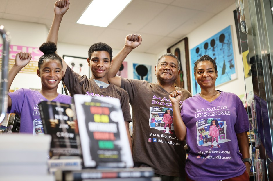 Malik Muhammad runs his bookstore in Los Angeles with his wife April and children Mecca (left) and Zahir.