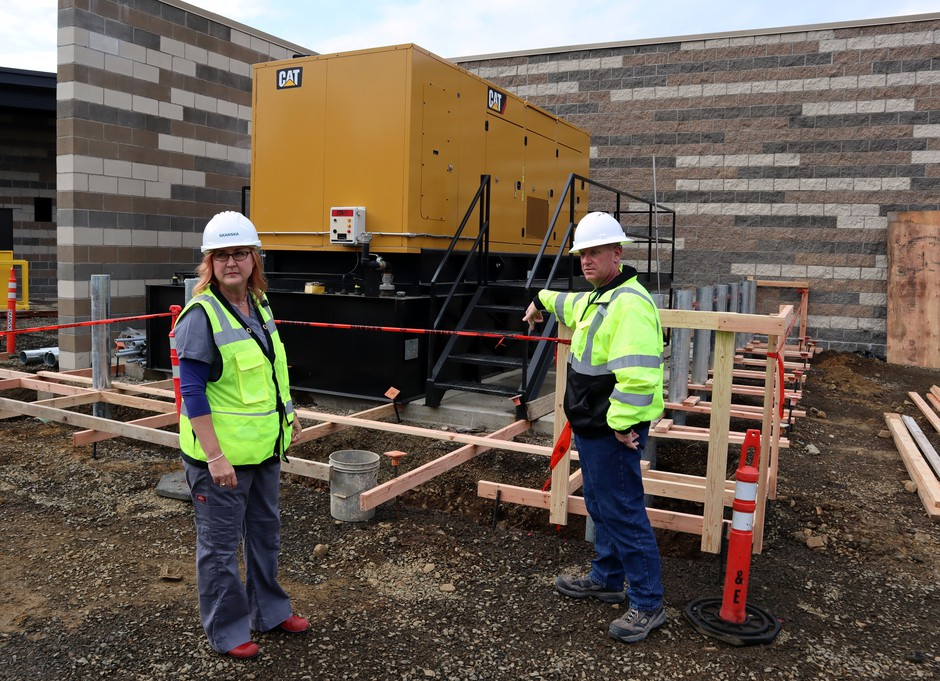 Dr. Lesley Ogden and Chris Lemar stand beside the backup generator at Lincoln City's new hospital, which is mounted on a shock-absorbing rack to protect against an earthquake.