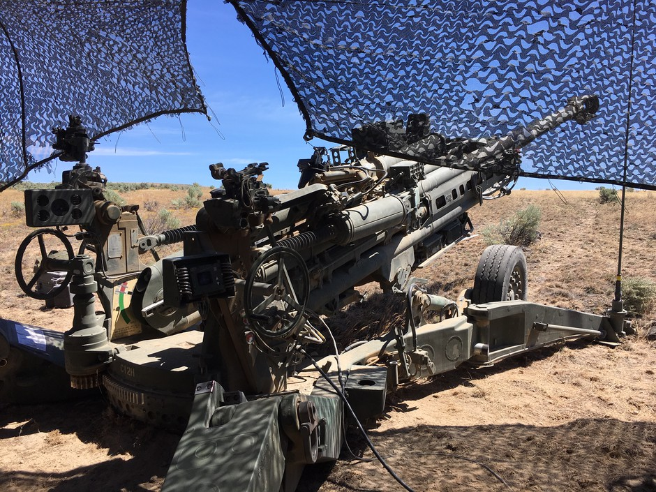 An M777 howitzer long-range gun is set up under a camouflage netting at the Yakima Training Center.