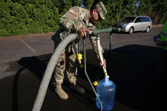 A National Guard soldier fills a container of water in the parking lot of a bowling alley in Salem.
