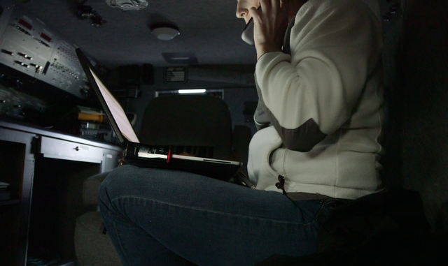 Washington Department of Fish and Wildlife Det. Wendy Willette investigating a shellfish trafficking case from inside a surveillance van. Willette's work sometimes requires going undercover. She agreed to be photographed on the condition that her face not be fully visible.