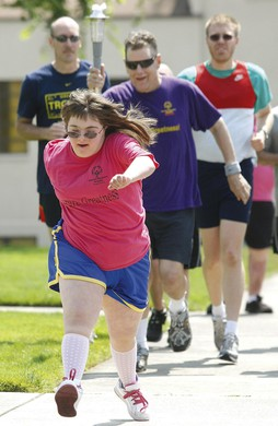 Jessica Rambaum, 17, of Roseburg, Ore. leads the way as Jerry Vanderhoff of Winston, Ore., carries the Special Olympics torch on Tuesday, July 10, 2012.