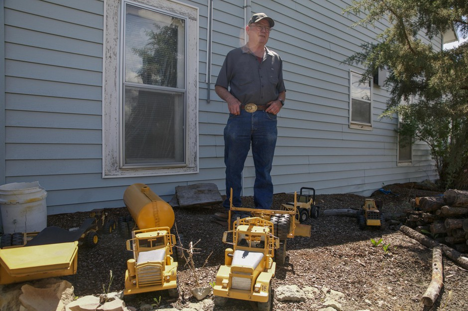 Otis Cody poses for a portrait with his model trucks in the front yard of his Fossil, Ore., home Tuesday, June 4, 2019. Cody has meticulously recreated model trucks reminiscent of those from the former company town of Kinzua.