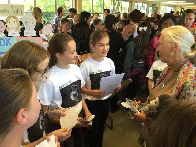 "Brooke Abbruzzese (reading from page) and Talia Baskin (red ponytail band) present the girls' ""Saving Pan"" cookbook project to Dr. Jane Goodall during a Roots & Shoots event at David Douglas High School in Portland, Oregon, on Oct. 15, 2015. In early 2018, they donated $10,000 from its sales to benefit Goodall's chimpanzee rehabilitation center and sanctuary in the Republic of Congo."