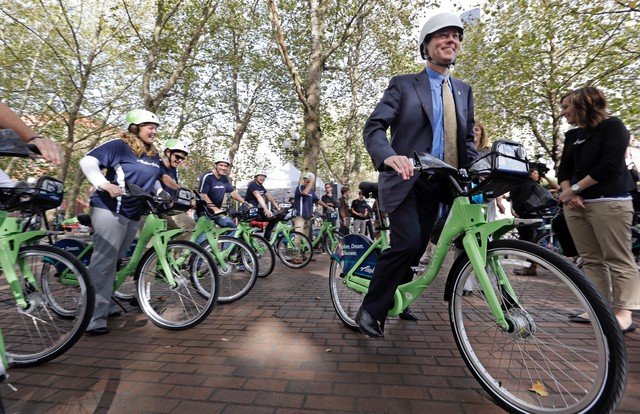 Brad Tilden, right, CEO of Alaska Airlines, lead a group of cyclists on an inaugural ride on new rental bikes, Oct. 13, 2014, in Seattle.