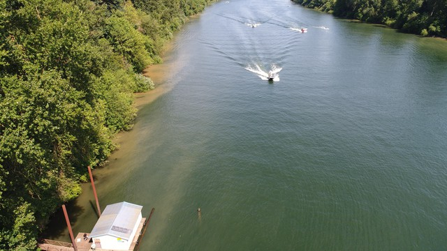 An aerial image illustrates erosion along the bank of the Willamette River.