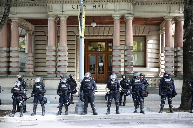 Portland Police in riot gear stand guard in front of Portland City Hall.