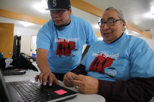 Scott Kalama helpsLouie Pitt fill out a census form online in Warm Springs, March 12, 2020.