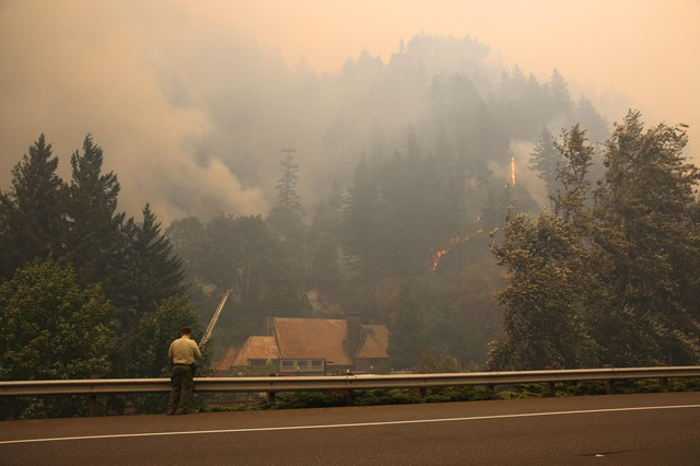 An officer looks on as fire crews work to keep the Eagle Creek Fire away from the Multnomah Falls Lodge Tuesday, Sept. 5, 2017.