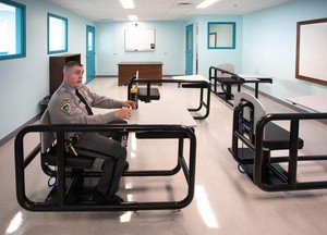 Correctional Capt. Toby Tooley demonstrates how the desks work at a behavioral health treatment center that opened in August at Oregon State Penitentiary in Salem.