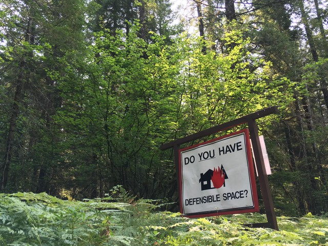 """A roadside reminder in southwest Washington's Gifford Pinchot National Forest that homes in the """"wildlands urban interface"""" need special landscaping, building materials and maintenance to reduce the risk of being destroyed by a wildfire."""