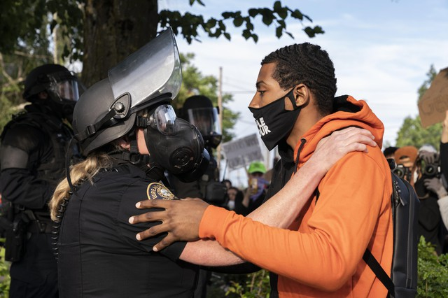 Linton McCallister embracing an officer at a protest prompted by the death of George Floyd outside of the Multnomah County Sheriff's Office on May 31, 2020.