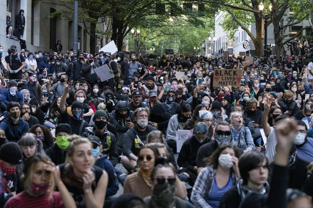 Massive crowds gathered in Portland for a fourth evening of protests over the killing of George Floyd, a Black man from Minneapolis who was killed after an officer pushed his knee into his neck for nearly nine minutes on June 1, 2020. Unlike previous nights of protests, there was a limited police presence on Portland streets, and demonstrators remained peaceful throughout five hours of marching.