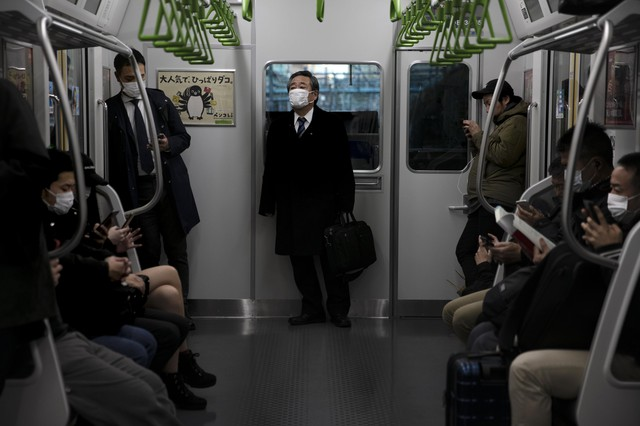 People wearing masks commute in a train in Tokyo, Tuesday, March 3, 2020. The Japanese government has indicated it sees the next couple of weeks as crucial to containing the spread of COVID-19, which began in China late last year.(AP Photo/Jae C. Hong)