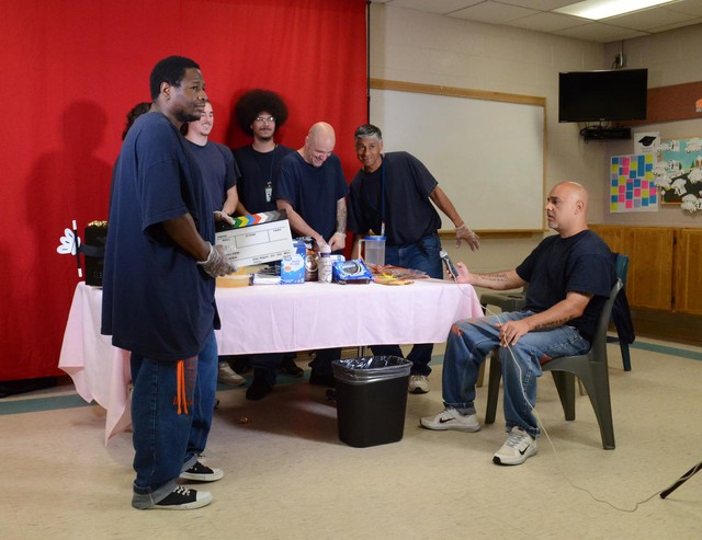 """Inmates at the Columbia River Correctional Institution on the set of """"The Inside Show,"""" a variety show produced in the prison. (From left) David """"Ohio"""" Phipps, Jason Melcado (hidden), Scotty Freeman, Gabriel """"Chino"""" Whitford, Michael """"HM"""" Lovett, Eugene """"Scooby"""" Brown, and Irvin Hines."""