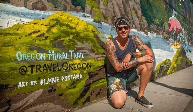 Artist Blaine Fontana poses in front of The Dalles mural located at the Mount Hood Railroad.