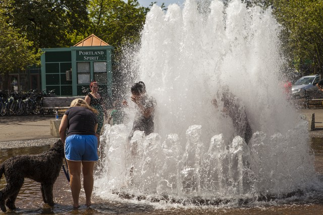 Young women run through the Skidmore fountain to cool off on a sunny day.