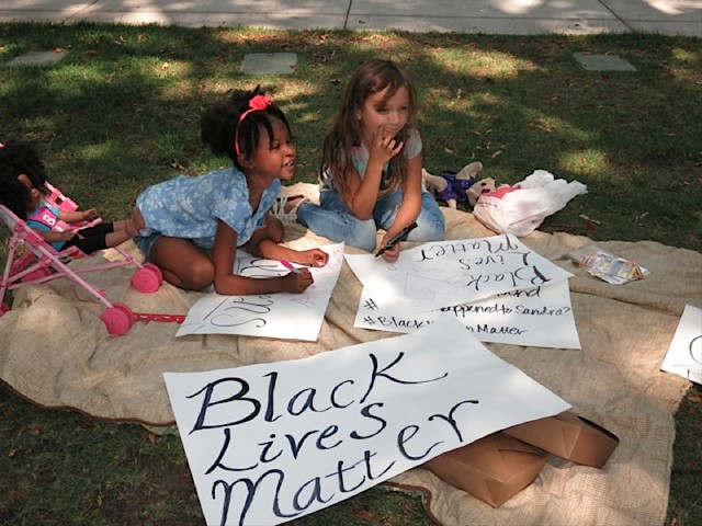 Kids making signs in the park for the 'Don't Shoot PDX' rally.