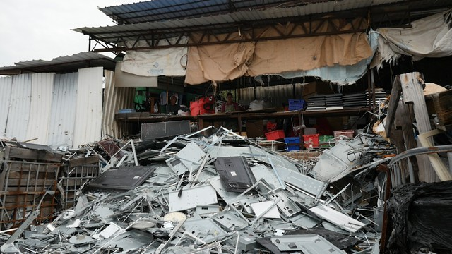 A pile of scraps from dismantled flatscreen televisions sits in front of workers at a junkyard in Hong Kong. Using a GPS location tracker, the environmental group Basel Action Network tracked a television from the Seattle-based recycler Total Reclaim to this junkyard.