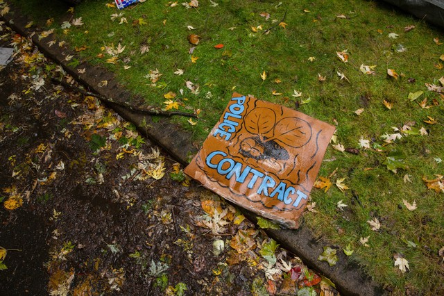 A sign on the ground outside of former Portland Mayor Charlie Hales' house left after a 2016 protest on his lawn over the city's latest police contract.