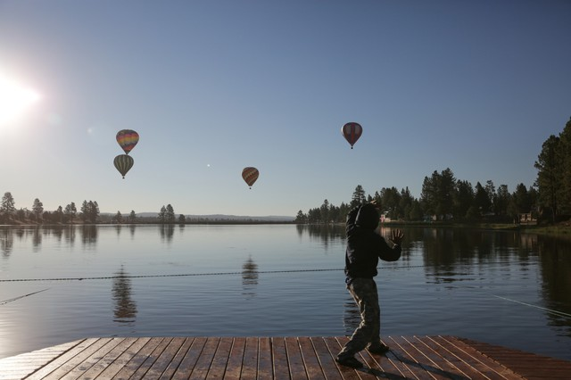 A man does tai chi as hot air balloons lift off over the lake at Big Summit Prairie in Central Oregon.