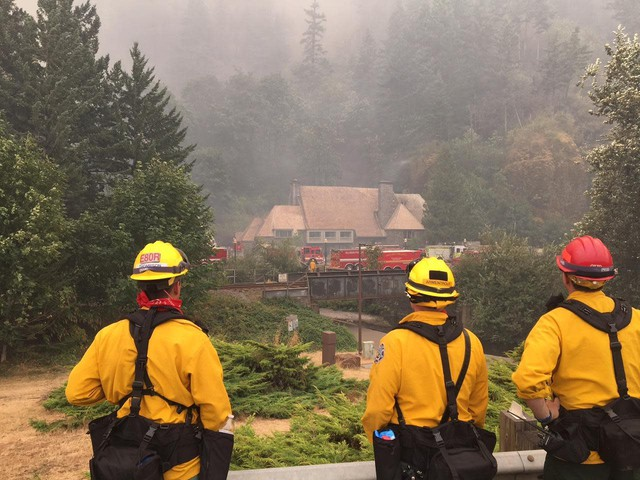 Firefighters survey efforts to save the Historic Multnomah Falls Lodge Tuesday, Sept. 5, 2017. Crews successfully saved the lodge from the Eagle Creek Fire after an all-day effort Tuesday.