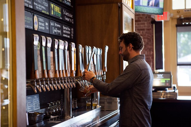 A bartender pours a beer at Widmer Brothers Brewing in Portland. Widmer is one of several Oregon businesses creating an alliance to combat climate change.