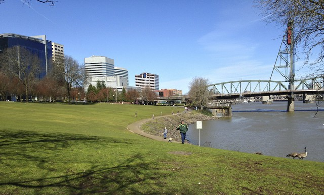 In this March 17, 2016 photo, a man walks along a pathway beside the Willamette River in Portland, Ore. Fiercely protective of its reputation as one of the most eco-friendly cities in the country, Portland is reeling from the discovery of poisonous heavy metals in the air and the ground of neighborhoods where thousands of people live, work and attend school.