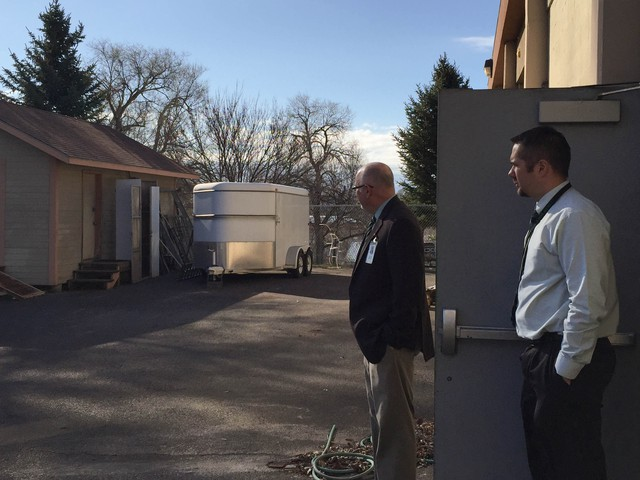 Pendleton Superintendent Jon Peterson (right) and Pendleton High School principal Dan Greenough look over a storage lot next to the high school. It used to be full of student projects. With the wood shop closed, there's little here.