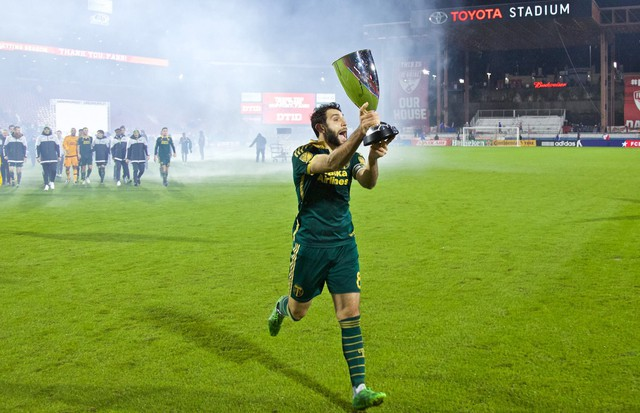 Portland Timbers midfielder Diego Valeri (8) carries the Western Conference Championship Trophy over to the Timbers Army at Toyota Stadium.