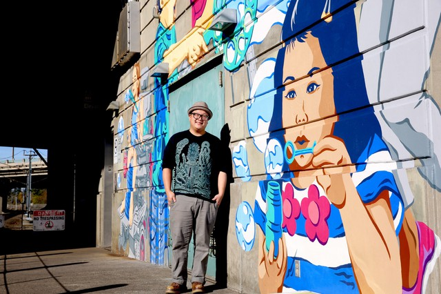 Alex Chiu stands by his mural at the platform of the 82nd Avenue Max Train Station.