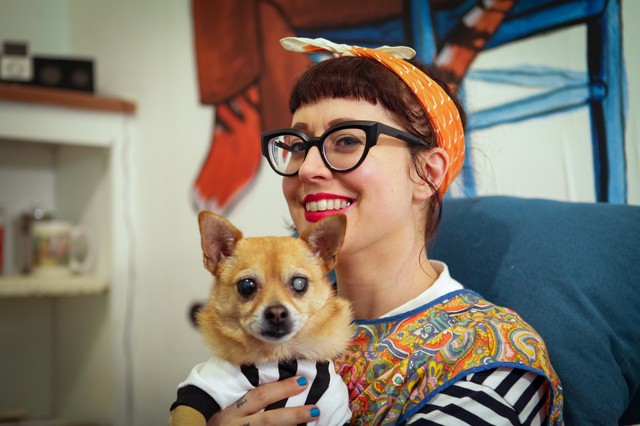 Graphic novelist, Nicole Georges, and her dog, Ponyo, seated in her Los Angeles studio.
