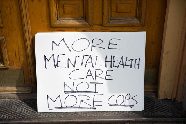 "A sign that sits out the entrance of the Cityteam Ministries Shelter reads ""More Mental Health Not More Cops."""