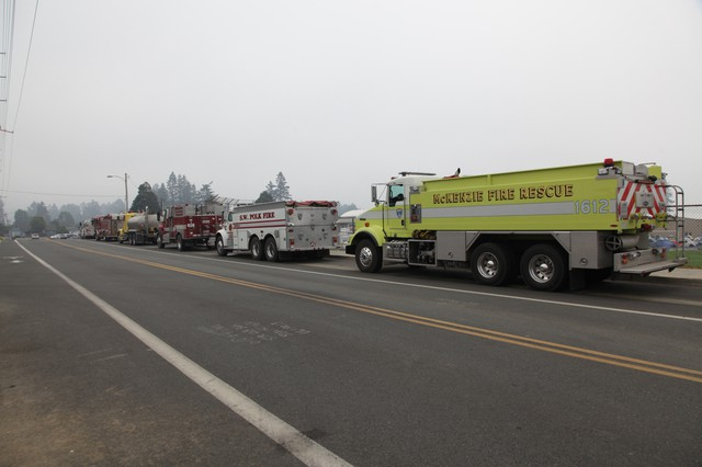 Water tankers and other firefighting trucks line up outside the high school in Brookings.
