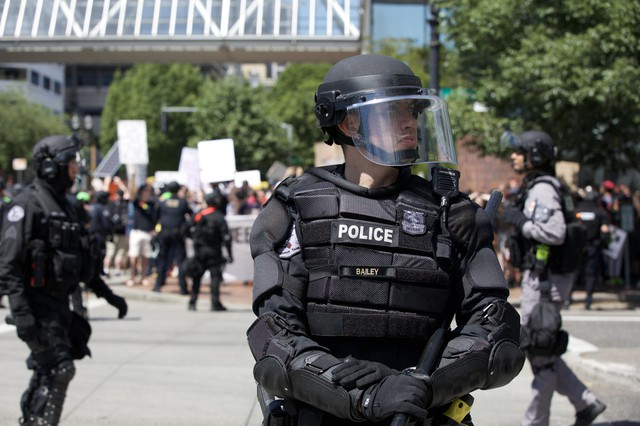 A Portland Police officer tries to keep right wing protesters and counter-demonstrators separate at dueling protests Aug. 4, 2018.