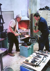 Arnon Kartmazov striking a hot piece of steel with a Japanese blacksmith.