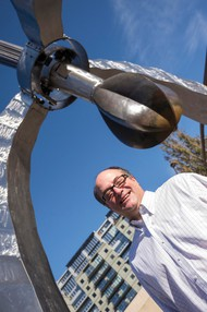 "Keith Lachowicz stands in front of ""Pod,"" the 11-year-old steel, titanium and bronze sculpture in the traffic triangle across from Powell's Books on West Burnside Street. Lachowicz is the public art collections manager for the Regional Arts & Culture Council."