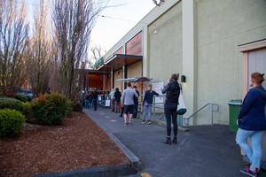 Shoppers stand in line outside Whole Foods in Portland, Ore., on Thursday, March 19, 2020. Grocery stores around the region have implemented social distancing guidelines during the new coronavirus pandemic, such as making customers stand 6 feet apart and limiting the number of people inside.