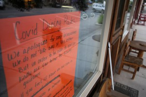 """A sign declares Covid Dining Rules at a cafe in Prairie City, Oregon: """"We do not like any of this either."""""""