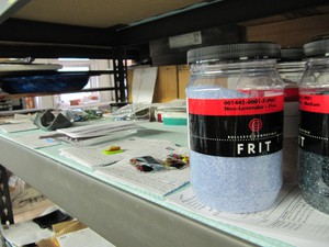 Colored frit, a raw material commonly used in glass-making, sits on a shelf at the Bullseye factory.