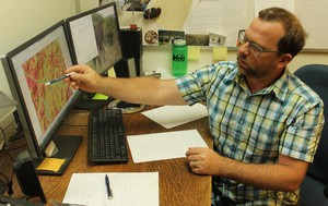 Oregon State University professor Chris Dunn examines a mapof the likelihood ofsuccess for fire suppression in southern Oregon. Dunn is part of a Forest Service team using data to improve decision-making and risk assessment.