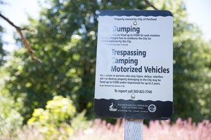 """A city sign posted at the entrance to a homeless camp on the Springwater Corridor bike path. Someone has spray painted it so it no longer reads """"No Camping."""""""