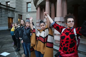 Arcadia Trueheart, Taylor Toro, and Molly Silverstein hold hands outside Portland City Hall. Protesters have called for Portland to be a sanctuary city for undocumented immigrants.