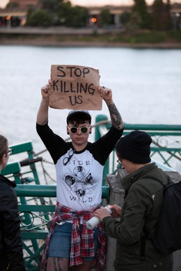 """Nikki Burian holds a sign inscribed with the words """"Stop Killing Us."""" """"It's a hate crime,"""" Burian said of the mass shooting at an Orlando gay nightclub."""