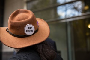 """A supporter displays a """"NOT GUILTY!"""" button following the not guilty verdict delivered in the trial of seven occupiers of the Malheur National Wildlife Refuge."""